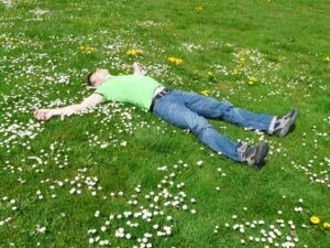 Man lying down on a daisy-filled patch of grass