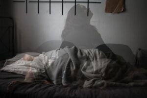 shadow of a woman sitting on an unmade bed